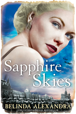 "Book cover for Belinda Alexandra's ""Sapphire Skies."" The main character, a beautiful platinum blonde woman with bold lipstick and blue eyes looks over her shoulder in a conspiratorial fashion. The skyline of Moscow lines the bottom of the scene and the bright sky creates a dramatic background."
